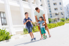 Happy young father with his two sons. Happy young father,a brunette with short hair, spends time on the street in the summer with his two sons,boys 5-7 years old Royalty Free Stock Image