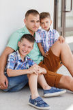 Happy young father with his two sons. Happy young father,a brunette with short hair, spends time on the street in the summer with his two sons,boys 5-7 years old Royalty Free Stock Photos