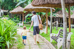 Happy young father holding his little son hand and walking on road. In a park Stock Images
