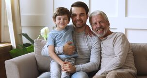 Smiling excited three male generations family resting on couch.
