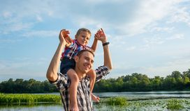Happy young father holds his son piggyback ride on his shoulders. Looking up and laughing. Little boy is sitting piggyback on shoulders his dad at river royalty free stock photos