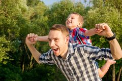 Happy young father holds his son piggyback ride on his shoulders. Looking up and laughing. Little boy is sitting piggyback on shoulders his dad while imitating stock photos