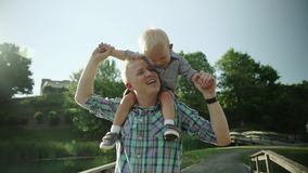 Happy young father holds his son piggyback ride on his shoulders and looking up. Little boy is sitting piggyback on