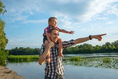 Happy young father holds his son piggyback ride on his shoulders. Points at something with his hand and laughing. Little boy is sitting piggyback on shoulders stock photography