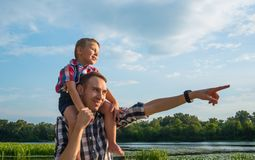Happy young father holds his son piggyback ride on his shoulders. Points at something with his hand and laughing. Little boy is sitting piggyback on shoulders stock images