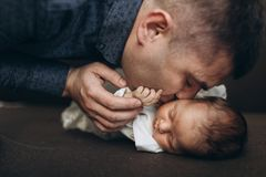 Father kisses her little babygirl. Happy and young father kiss his cutie small babygirl Royalty Free Stock Photography
