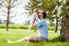 Happy young father kissing little son in park. Portrait of happy young Caucasian father sitting on grass, holding little newborn son and kissing him in park Stock Image