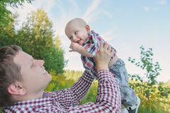 Happy young father lifting up his son. Happy young father holding up in his arms little baby putting him up. Outdoor portrait. Happiness and harmony in family Stock Images