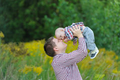 Happy young father lifting up his son. Happy young father holding up in his arms little baby putting him up. Outdoor portrait. Happiness and harmony in family Stock Image