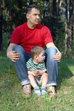 Happy young father with little cute son sit on grass Stock Photos