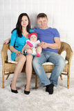 Happy Young Father, Mother And Baby Sit On Sofa At Home. Royalty Free Stock Photos