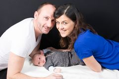 Young father mother and cute baby boy lying on floor hug and kiss parent. Happy young father mother and cute baby boy lying on floor hug and kiss parent Stock Photo