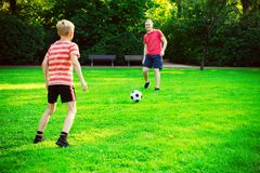 Happy young father play with his little son football in sunny pa. Happy young father play with his little son football in green sunny park royalty free stock photos