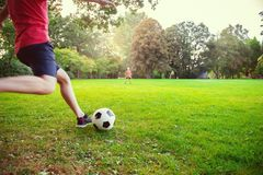 Happy young father play with his little son football in sunny pa. Happy young father play with his little son football in green sunny park stock images