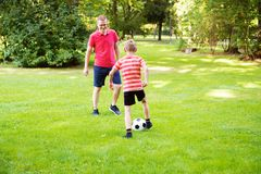 Happy young father play with his little son football in sunny pa. Happy young father play with his little son football in green sunny park royalty free stock images