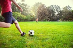 Happy young father play with his little son football in sunny pa. Happy young father play with his little son football in green sunny park stock photography