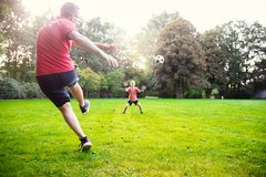 Happy young father play with his little son football in sunny pa. Happy young father play with his little son football in green sunny park royalty free stock image