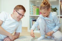 Happy young father playing with his cute little daughter at home stock photo