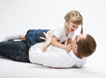 Happy young father playing with his smiling daughter Stock Photos