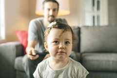 Happy young father on the sofa with tv remote and little daughter stock photography
