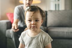 Happy young father on the sofa with tv remote and little daughter royalty free stock photography