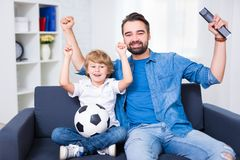 Happy young father and son watching football and celebrating goa. Happy young father and son watching football on tv and celebrating goal Stock Images