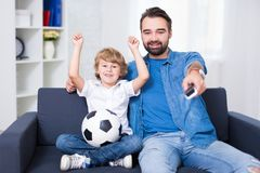 Happy young father and son watching football. On tv Stock Photography