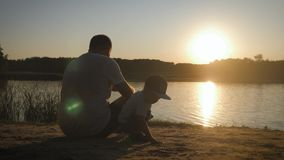 Happy young father spending time together with his little sonby the river on the sandy beach. Silhouette of father and stock video