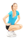 Happy young female athlete on a weigth scale looking at camera Royalty Free Stock Image