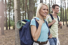 Happy young female backpacker with man hiking in woods Royalty Free Stock Images