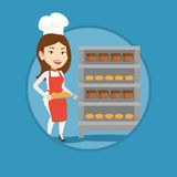 Happy young female baker holding tray of bread. Royalty Free Stock Image