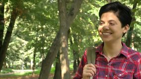 Happy young female college student with short hair walking in park and smiling, beautiful nature and sunny weather stock footage