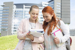 Happy young female college students studying in park with building in background Royalty Free Stock Image