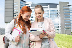 Happy young female college students studying in park with building in background Stock Photo