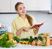 Happy young female with cookery book and veggies Stock Photography