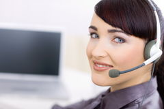 Happy young female customer service. Operator talking on headset, sitting in front of computer screen, smiling Stock Photos