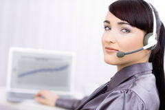 Happy young female customer service operator. Talking on headset, sitting in front of computer screen, smiling Stock Images