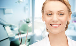Happy young female dentist with tools. People, medicine, stomatology and healthcare concept - happy young female dentist with tools over medical office Stock Photos