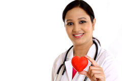 Happy young female doctor holding a beautiful red heart shape. Against white Royalty Free Stock Images