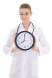 Happy young female doctor holding office clock isolated on white Stock Photos