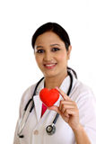 Happy young female doctor holding a red heart shape. Happy young female doctor holding a beautiful red heart shape stock photo