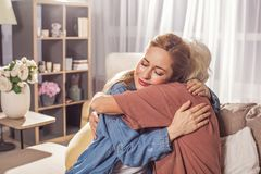 Glad girl hugging granny in room. Happy young female embracing mother while locating in living room. Cuddle concept Stock Photography