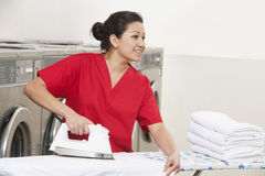 Happy young female employee ironing while looking away in Laundromat Royalty Free Stock Photography