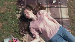 Happy young female with flowing hair lies near beautiful bouquet of flowers on bedspread on meadow and enjoy outdoor. Recreation, top view close up stock video