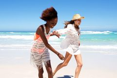 Happy young female friends running on beach Stock Photos