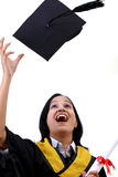 Happy young female graduate tossing up her hat Stock Image