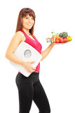 Happy young female holding a plate of vegetables and a weight sc Royalty Free Stock Image