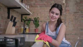 Happy young female housewife in rubber gloves for cleaning wipe dusty furniture on kitchen. Close-up stock video footage
