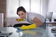 Happy Female Janitor Cleaning Desk With Rag stock images