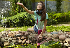 Happy young female listening to music at the park Royalty Free Stock Image